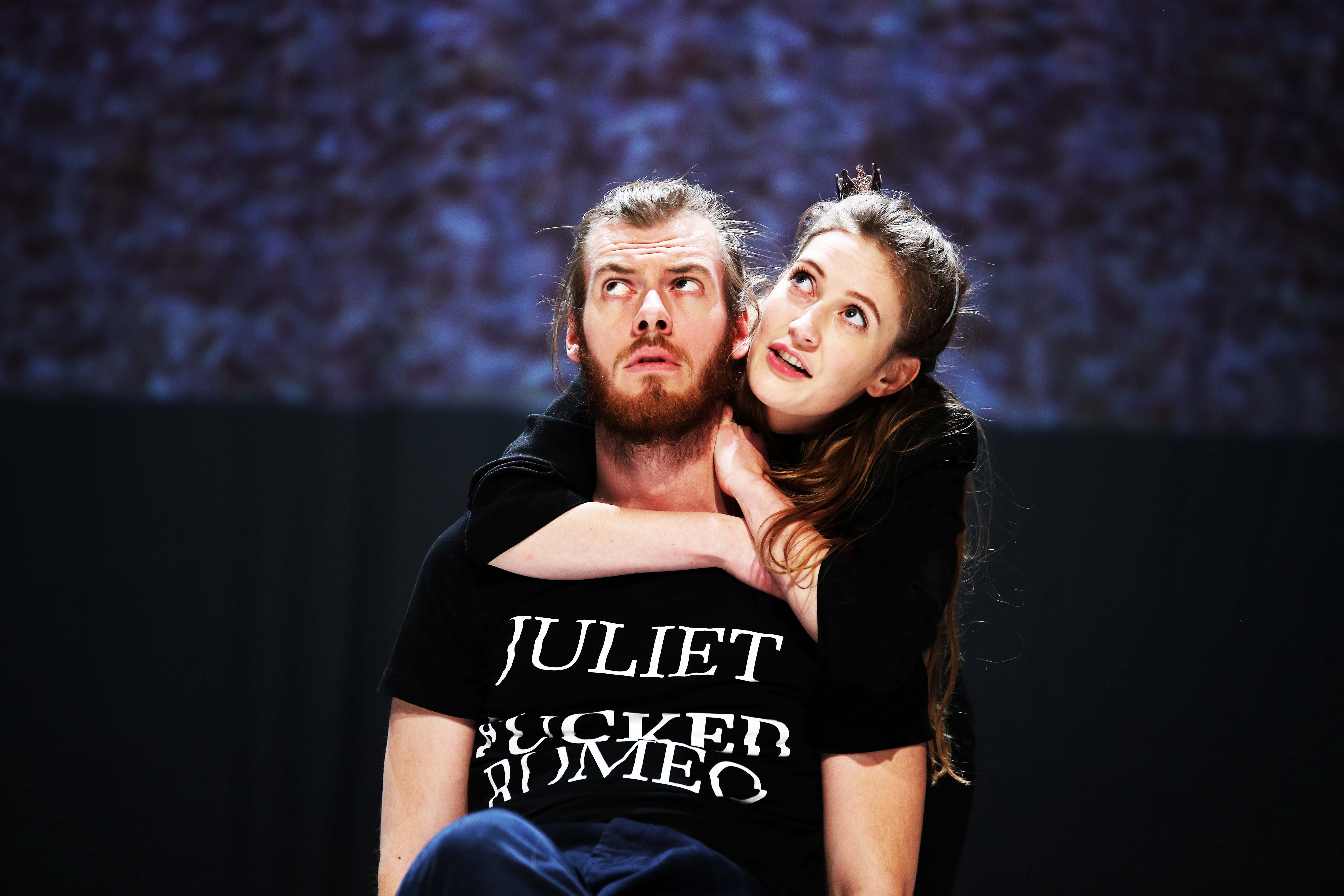 Ein Mann sitzt vor einem dunklen Hintergrund. Er trägt ein T-Shirt auf dem Juliet fucked Romeo steht. Eine Frau umarmt ihn von hinten. Beide gucken erwartungsvoll nach oben.