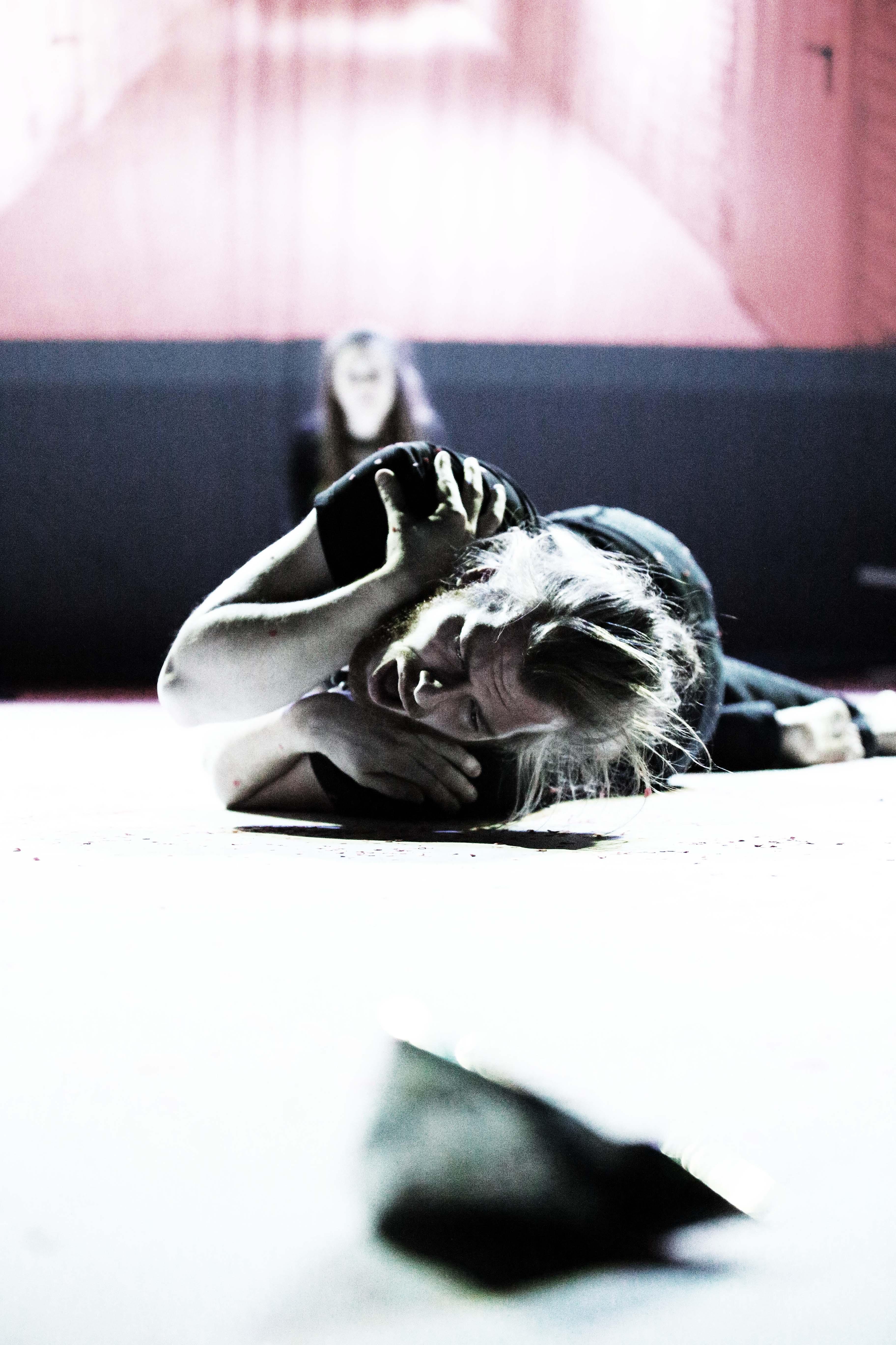 Der gleiche Mann liegt auf dem Boden. Er schreit oder weint. Im Hintergrund ist die Frau zu erkennen. Der Hintegrund ist schwarz rot getränkt.